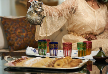 A woman Pours Moroccan Tea from Traditional moroccan Teapot into cups.