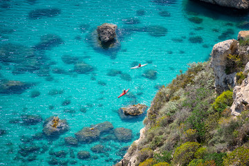 Aerial view of crystal clear blue sea with canoeists