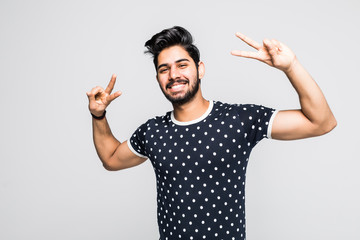 Portrait of happy young indian man showing victory on white background