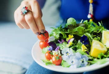 a woman eating fresh tasty vegan vegetarian salad flowers and tomatoes, dieting, fitness, healthy food