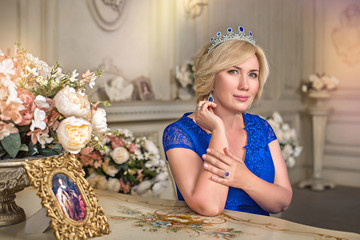 Portrait of delightful blonde woman with diadem, in blue dress, sits at table, in luxurious room with rose flowers