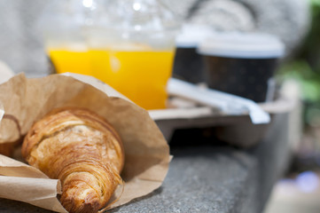 Croissant breakfast with coffee and orange juice to take away
