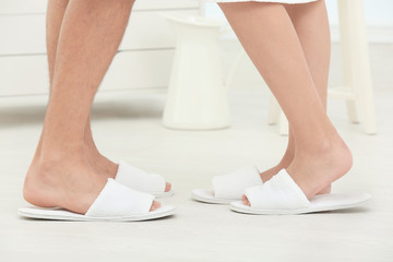 Young loving couple in bathing slippers on floor