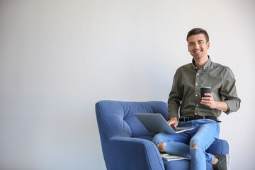 Young blogger with laptop sitting on armchair against light wall