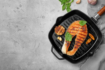 Frying pan with tasty salmon steak on grey background