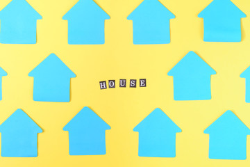 Empty blue stickers in the shape of a house on a yellow background. In the center there is an inscription HOUSE. Bright beautiful layout, mock up. Photo from the top.