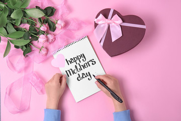 "Child writing phrase ""HAPPY MOTHER'S DAY"" in notebook near gift and roses on table"