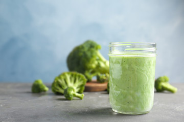 Jar with healthy detox smoothie and broccoli on table