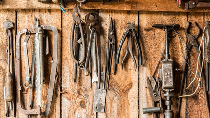old working tool on the background of wooden panels, the tools of the artisan hang on nails