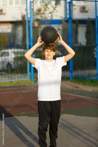 cute sporty teenage european boy playing basketball outdoorscute sporty teenage european boy playing basketball outdoors preparing for shooting active lifestyle