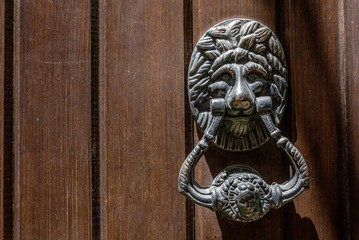 Detail of an old door in brown wood with iron handle and lion face.