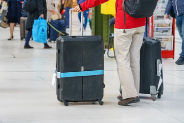 Close-up of young woman hands holding suitcase in modern airport terminal. Travelling guy wearing smart casual style clothes standing with his luggage while waiting for transport