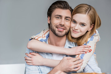 portrait of young woman hugging boyfriend from behind
