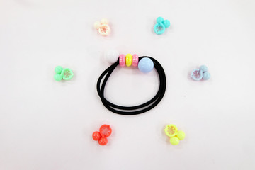 Black Rubber Band with Bead Fashion Accessories. Hair Elastic Band with Free Space. Black Hair Band with Colorful Hair Clip Isolated on Pink Background