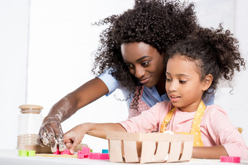 african american mom and daughter making cookies with cookie cutters together