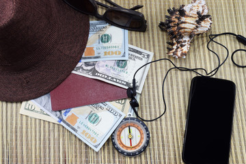 preparation for the holiday, a passport with money for rest on the table and a cell phone on the road, a hat and sunglasses from the sun