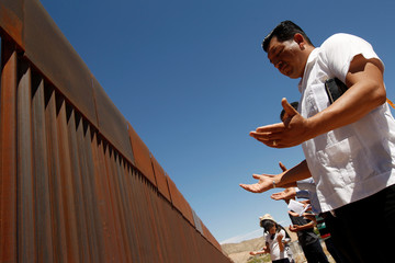 Members of the Presbyterian church pray at a new section of the border wall on the U.S.-Mexico border during a liturgy to commemorate the religious dimensions of migration, in this picture taken from Anapra neighborhood in Ciudad Juarez