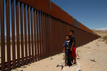 Children stand by a new section of the border wall on the U.S.-Mexico border in this picture taken from Anapra neighborhood in Ciudad Juarez