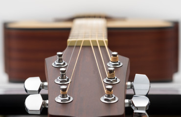 An acoustic guitar headstock on white background.