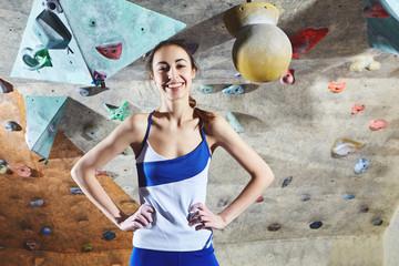 woman climber posing indoors on climbing gim