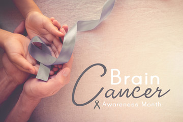 Adult and child hands holding gray ribbon, Brain Cancer Awareness month