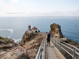 Fit caucasian man, age 50, taking photo of cliffs and ocean with mobile phone at Point Reyes lighthouse, Marin County, California.