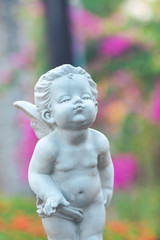 Cupid stone statue in the flower garden.
