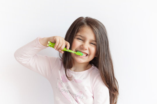 Little cute child girl brushing her teeth on white background. Space for text. Healthy teeth.