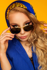 fashion portrait of a beautiful blonde in a blue scarf and jacket in sunglasses
