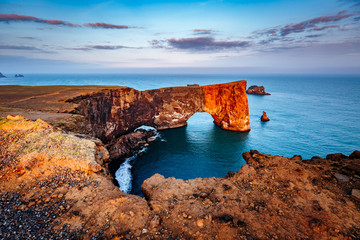 Amazing black arch of lava standing in the sea. Location cape Dyrholaey, Iceland, Europe.