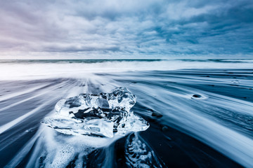 Large pieces of the iceberg that sparkle on the black sand. Location place Jokulsarlon, Vatnajokull national park, Iceland.
