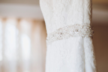 Close-up of fashionable white wedding dress on a hanger in hotel room, morning wedding preparation concept