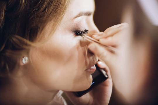 make up. bride getting on her make-up on by professional artist, morning preparation. beautiful bride in robe talking on phone and hand with tweezers putting on eyelashes