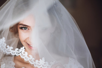happy stylish bride smiling and looking under veil. space for text. gorgeous emotional bride getting ready and having fun in the morning