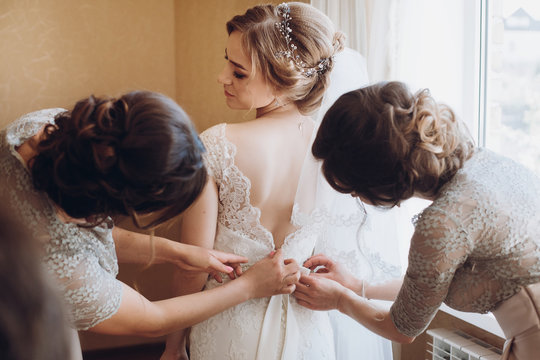 bride getting ready in the morning. bridesmaids helping bride put on lace wedding dress, back view. happy girls at the window before wedding
