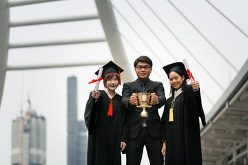Portrait of Two happy graduated young girls in graduation gowns holding diplomas and smile together in city with  and one man hold the trophy