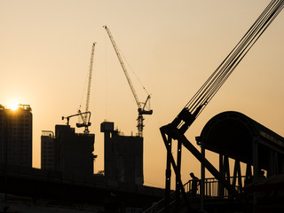 Cranes working on Building Construction site sunset sky Silhouette Industrial background