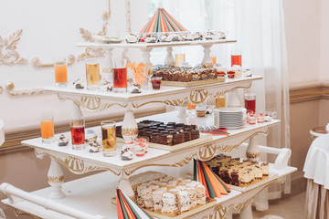 delicious cakes cupcakes juice and desserts sweet on table at wedding reception in restaurant. luxury catering. christmas feast. wedding candy bar