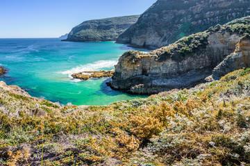 Tasman Peninsula, Tasmania, Australia: Scenic coastline of rocky cliff Tasman arch with old stone formations dramatic structures near blue wild ocean perfect hiking landscape countryside Port Arthur