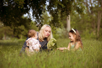 Mother's day. Mom with daughters on a background of green grass