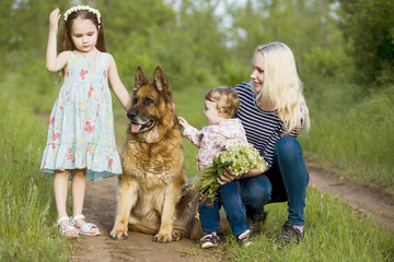 Mother day. Mother with two daughters and a dog, a German Shepherd on a green grass