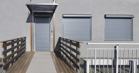 Metal blinds on the doors and windows of the facade of the house