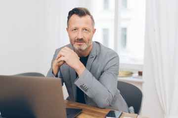 Portrait of mature man sitting in front of laptop