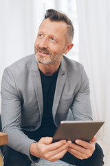 Smiling mature man using digital tablet