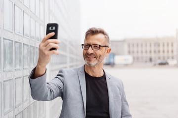 Portrait of cheerful mature man taking selfie