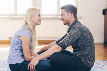 Blonde woman with sitting in front of man at home