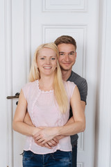 Home portrait of young smiling couple