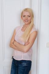 Portrait of blonde woman standing against door