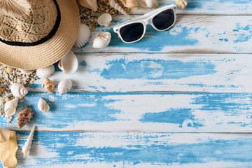 Seashells on blue wooden board with straw hat and sunglasses. Summer holiday background.