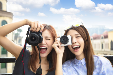 two happy girls holding camera and travel concept